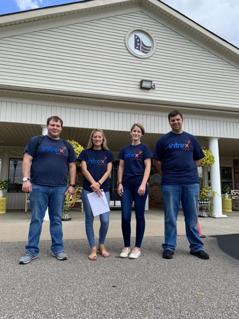 Intrex team smiling outside of a senior living community