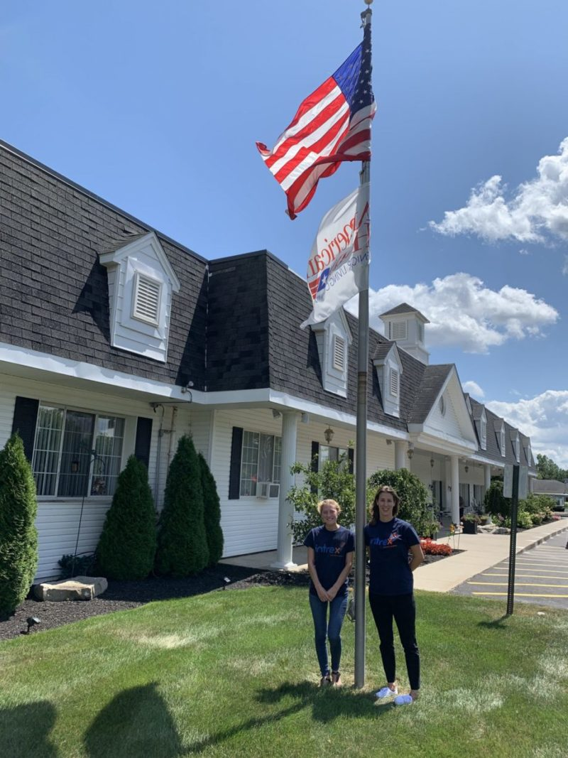 2 Intrex employees and the American flag outside of a senior living community