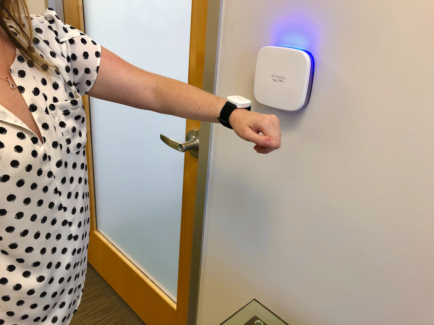Rythmos wearable worn on woman's wrist being used to unlock a door with Rythmos access control reader