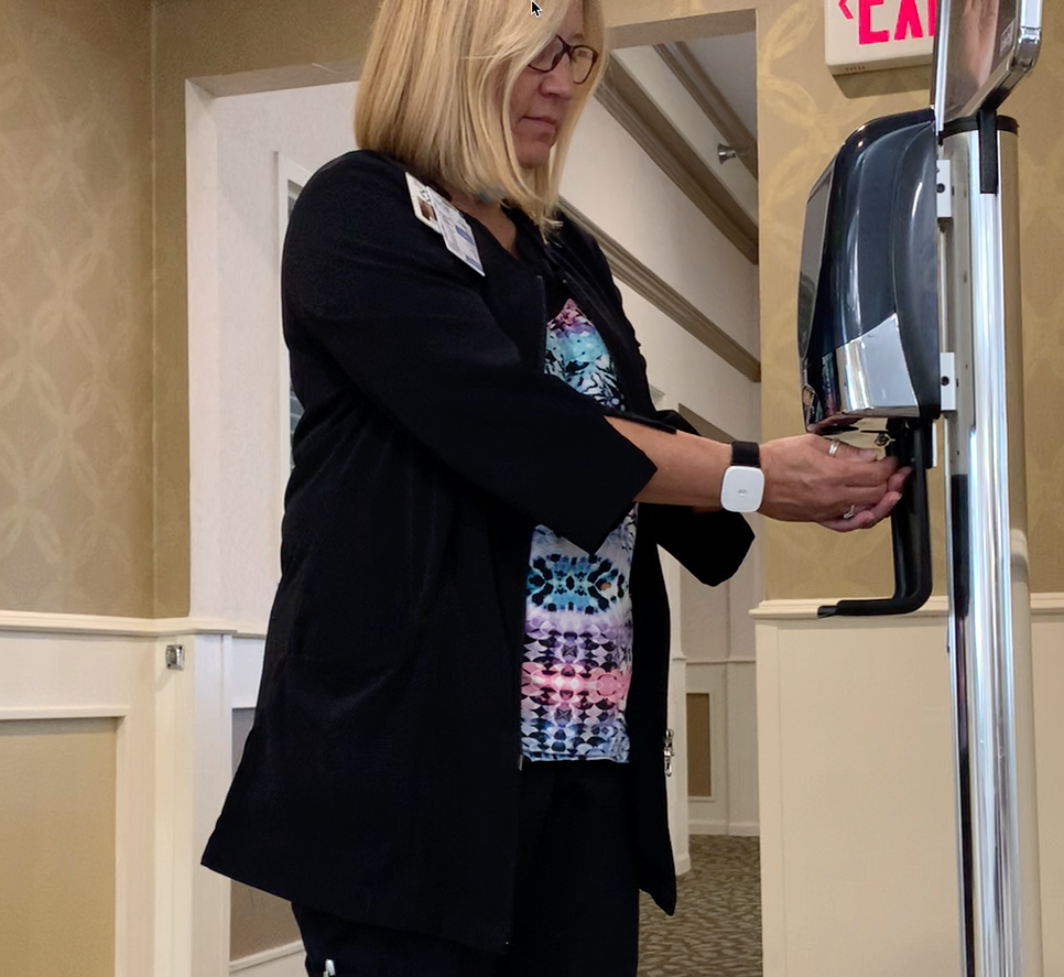 Nurse with Rythmos wearable sanitizing her hands