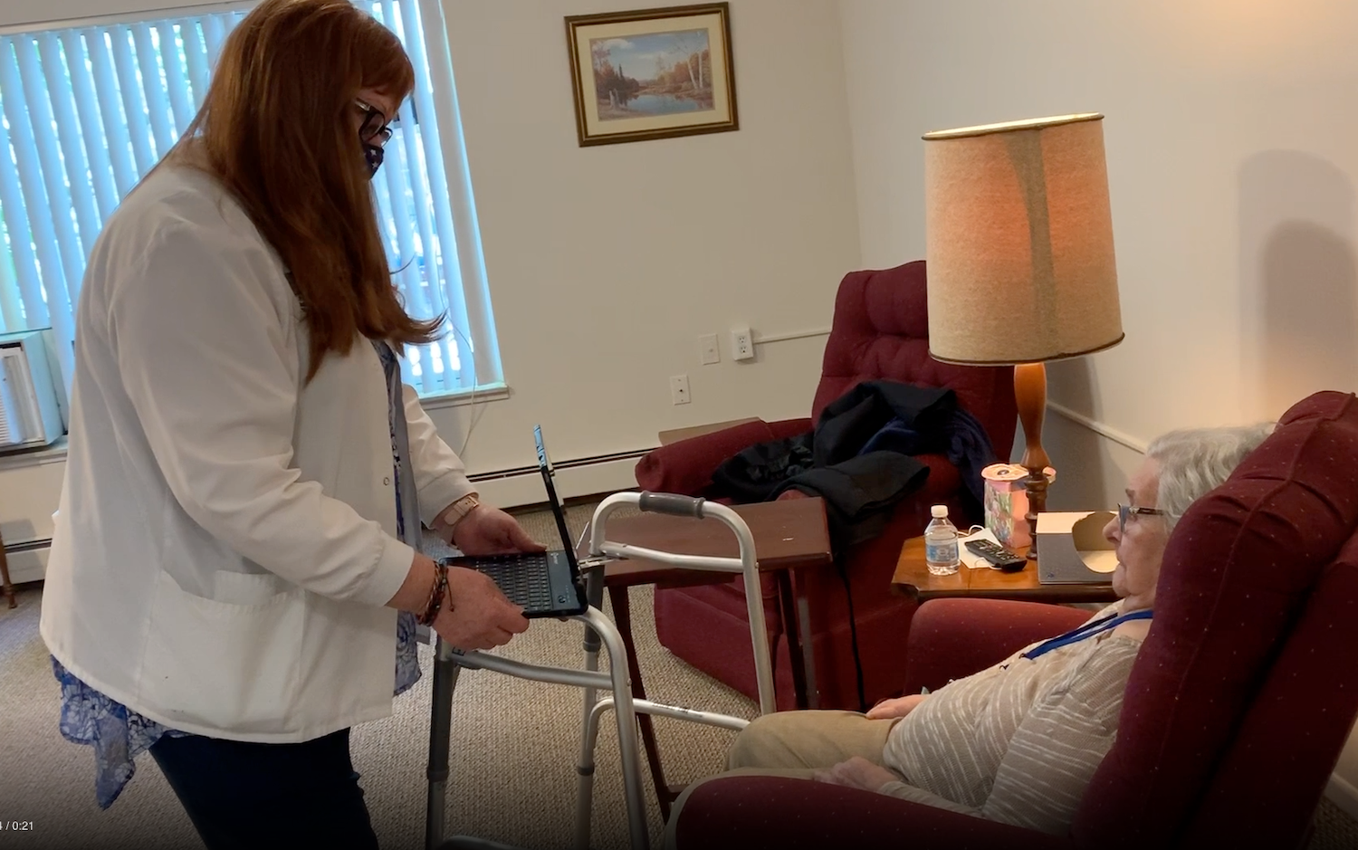 Nurse with iPad helping a Senior woman video chat with family