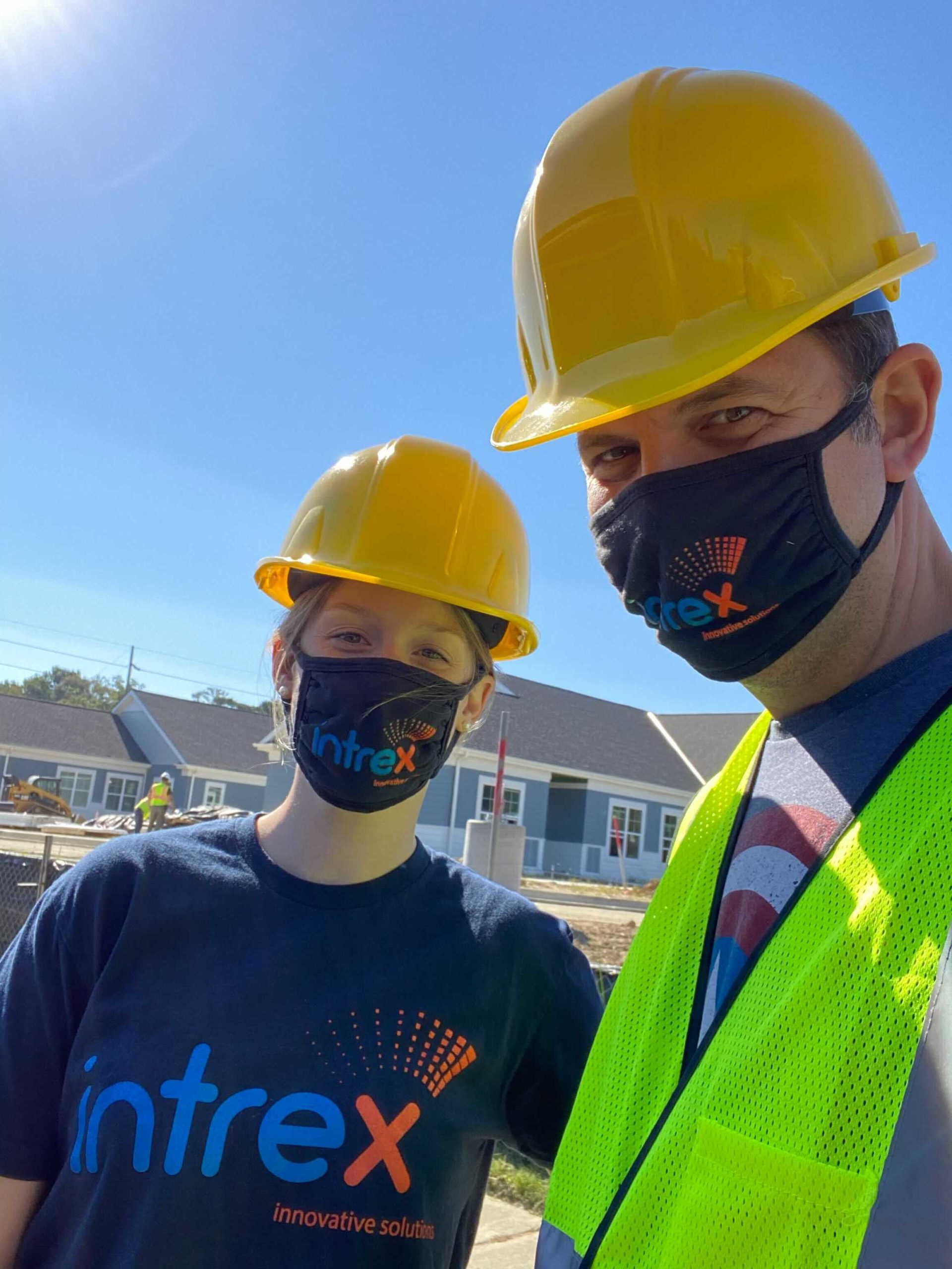 Intrex employees with hard hats and masks at a new construction site